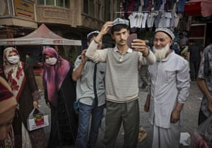 A Uighur man tries on a new traditional hat as he buys new clothes before the Eid holiday.