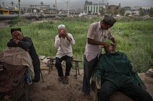 A Uighur barber shaves a customer at an outdoor stall.