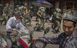 Chinese soldiers march near the Id Kah mosque, China's largest.