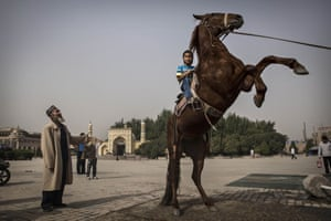 A boy rides a horse as he has his picture taken outside the Id Kah Mosque.
