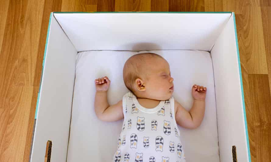 Young baby is sleeping in a Finnish maternity box that can be used as a first crib