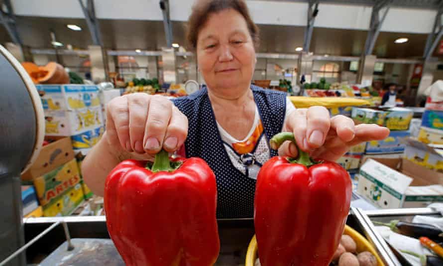 A vendor holds bell peppers from Crimea as she displays them at the city market in St.Petersburg