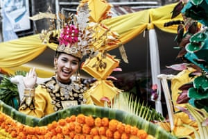 A participant waves to the crowd during Tomohon International Flower Festival in North Sulawesi, Indonesia