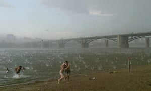 People run to shelter from hailstorm on the beach at Ob River, the major river in western Siberia in Novosibirsk, Russia, 2014