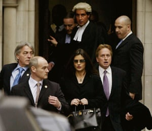 "Catherine Zeta-Jones and Michael Douglas leave the Royal Courts of Justice after testifying, 2003. The Welsh actress and her Oscar-winning husband are suing ""Hello!"" magazine for millions of pounds after it published unauthorised photos of their New York November 2000 wedding, for which they had signed an exclusive deal with rival magazine ""OK""."