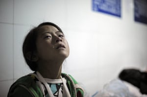 20 Photographs: An injured girl cries at Ludian hospital after the earthquake