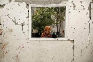 20 Photographs: A woman looks at a badly damaged house at the Jabaliya refugee camp