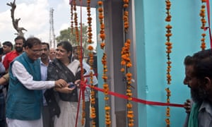 Bindeshwari Pathak, left, founder and chairman of NGO Sulabh International, cuts a ribbon to one of the new toilets.