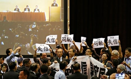 Pro-democracy MPs hold up signs during a protest as Li Fei explains China's electoral decision