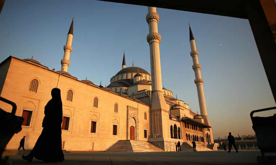 A woman walks past a mosque in Turkey