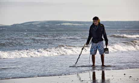 Metal detecting on Bournemouth beach, Bournemouth, England