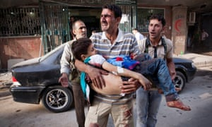 A father crying while holding his dead child in front of Dar al Shifa hospital in Aleppo, Syria.
