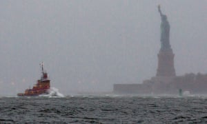 Waves crash over the bow of a tugboat as Hurricane Sandy approaches New York.