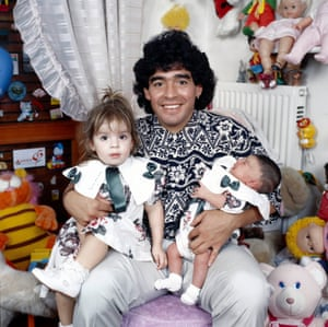 1989 Diego Maradona sitting in a small doll and cuddly toy infested bedroom with his daughters Dalma and Giannina in his arms.