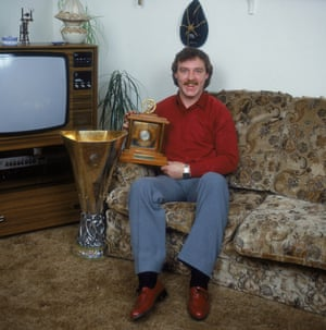 Ipswich Town's Kevin Beattie proudly holds his Young Player of the Year Award as he sits in the living room of his home.  The Uefa Cup is also lurking next to the sofa.