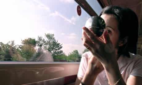 A woman applying makeup on a train