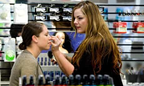 A woman applying makeup to a customer at a beauty counter