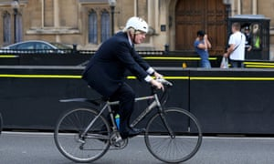 Boris Johnson, the mayor of London, rides his bicycle past the Houses of Parliament in 2013