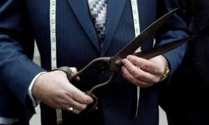 man in suit holding large pair of scissors