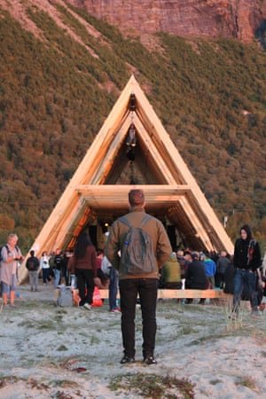A man watches a performance at SALT's main stage, one of three wooden prisms built specifically for the site. The structures are based on traditional fish-drying racks from the region.