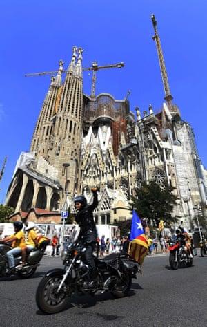 Bikers with estelada flags ride past the Sagrada Familia in Barcelona