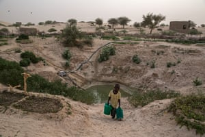 A young boy collects water from one of the few remaining waterholes on the outskirts of the city.