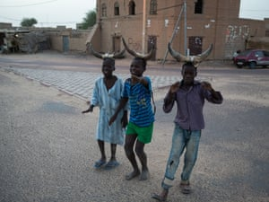 Children wearing horns play a version of 'trick or treat' during the first phase of Ramadan.