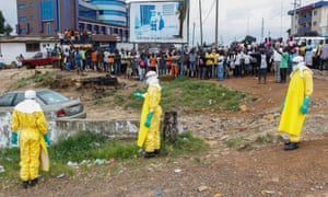 Health workers collect Ebola victim's body.