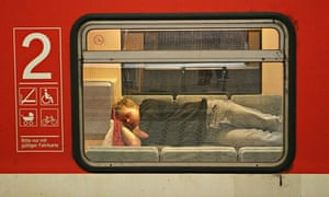A passenger sleeps in a train stationed at Augsburg's railway station, Germany.