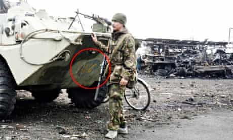 An unidentified pro-Russian soldier seen near an APC with a mark of peacekeeping troops