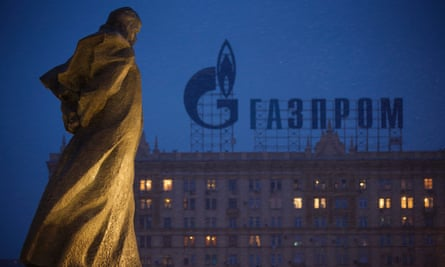A monument to Ukrainian poet and writer Taras Shevchenko is silhouetted against an apartment building with a sign advertising Russia's natural gas giant Gazprom, in Moscow.