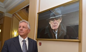 Northern Ireland First Minister Peter Robinson in front of a portrait of Ian Paisley at Stormont