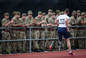Phillippe Robert of France is applauded by troops after winning the men's 100m ambulant IT2 final.