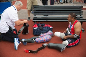 Derek Derenalagi of Great Britain has help swapping over the legs he uses for running with the ones he uses for throwing events after competing in the men's 200m ambulant IF2 final during the athletics competition.