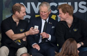 Prince William, Prince Charles and Prince Harry laugh at a phone message whilst watching in the stands.