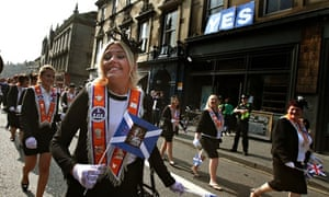 Women wave flags depicting the Queen on the Orange Order march