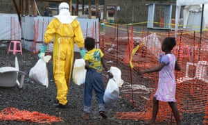 A medical worker wearing a protective suit carries bags followed by Ebola infected children in the high-risk area of the Elwa hospital runned by Medecins Sans Frontieres
