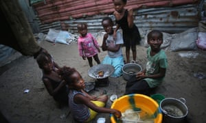 Children sit outside their homes in a favella in Liberia.