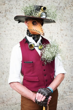 Mark Green, who works for DHL, wears a leather plague doctor's mask and bunches of gypsophila