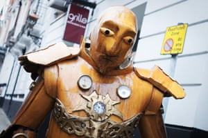 A man wearing an automaton costume made entirely out of carved wood