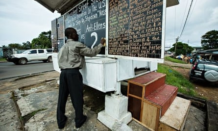 Alfred Sirleaf, a Liberian citizen journalist, with his chalkboard newspaper