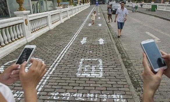 Vía en Chongqing, China, para ir leyendo o escribiendo sobre el smart phone (Fuente: https://i.guim.co.uk/img/static/sys-images/Guardian/Pix/pictures/2014/9/15/1410787901624/85296c07-cb3e-4ed7-9119-fb19f2d04b1b-bestSizeAvailable.jpeg?w=620&q=55&auto=format&usm=12&fit=max&s=904c9e75da40b704373832965b967296)
