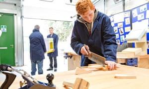 Jordan Lee Caffyn saws wood at a workshop in Surrey
