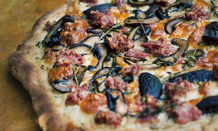 Smoked mozzarella and salsiccia pizza on a wooden table