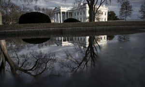 The White House is seen reflected in a puddle in Washington DC