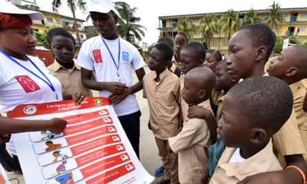 United Nations Development Programme volunteers show a placard about Ebola symptoms  to school students in Abidjan, Ivory Coast.
