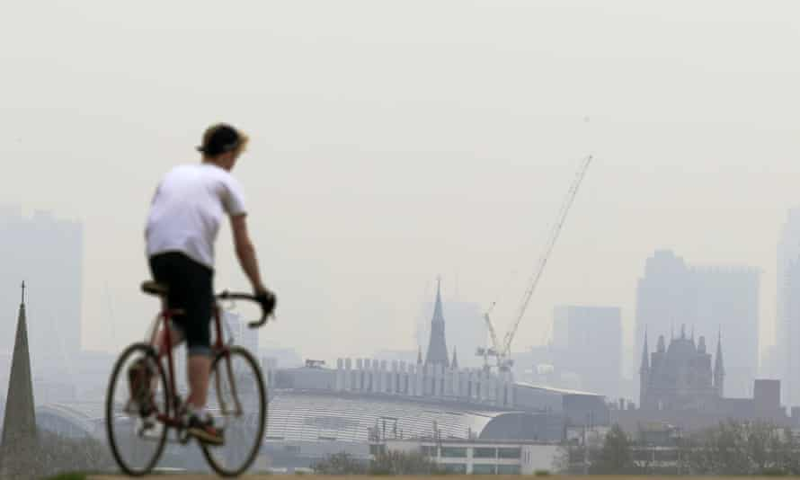 A cyclist rides his bike at the top of Primrose Hill in London on April 3, 2014, as the city below lies shrouded in pollution.