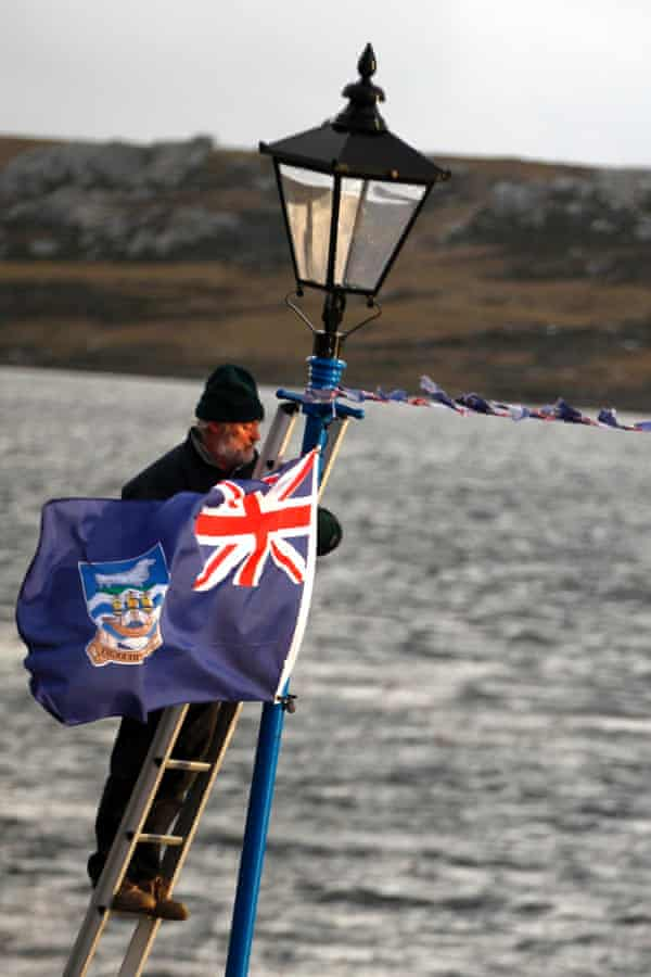 A man hangs a Falklands flag in Stanley to celebrate the 30th anniversary of the 1982 Falklands war.