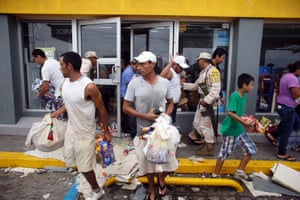 People loot a supermarket destroyed by hurricane Odile in Los Cabos