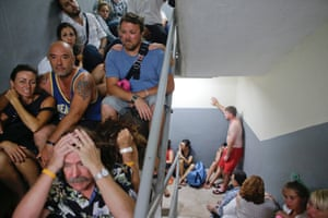 Tourists sit on the concrete stairs in the service area of a resort after the designated area for shelter was destroyed by winds in Los Cabos, Mexico
